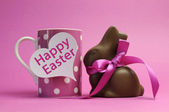 Happy Easter pink polka dot coffee or tea mug with white heart shape gift tag sign and chocolate bunny with pink ribbon, with Happy Easter message — Stock Photo
