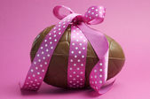 Happy Easter chocolate Easter egg with pink polka dot ribbon tied in a bow — Foto Stock
