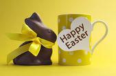 Thème jaune pois petit déjeuner tasse à café avec un lapin au chocolat et coeur message forme disant joyeuses pâques. — Photo