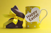 Yellow theme polka dot breakfast coffee mug with chocolate bunny rabbit and heart shape message saying Happy Easter. — Stock Photo