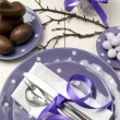 Purple theme Easter dinner, breakfast or brunch table setting with chocolate bunny rabbit, and sugar candy coated birds nest eggs on polka dot plates on white shabby chic natural wood table. - Stock Photo