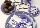 Purple theme Easter dinner, breakfast or brunch table setting with chocolate bunny rabbit, and sugar candy coated birds nest eggs on polka dot plates on white shabby chic natural wood table. — Stock Photo