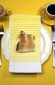 Amarillo tema feliz pascua mesa de desayuno con conejo conejo tostadas y huevo. vertical. — Foto de Stock