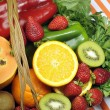 Healthy diet - sources of Vitamin C - oranges, strawberry, bell pepper capsicum, kiwi fruit, paw paw, spinach dark leafy greens and parsley. Vertical. — Stock Photo #21768115