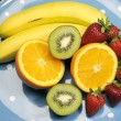 Platter of fruit - bananas, orange, kiwi fruit and strawberries - on blue polka dot platter for healthy diet and fitness. — Stock Photo #21768145