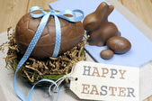 Happy Easter still life with chocolate eggs, bunny and gift tag on wood table. — Stock Photo