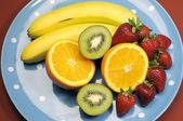 Platter of fruit - bananas, orange, kiwi fruit and strawberries - on blue polka dot platter for healthy diet and fitness. — Stock Photo