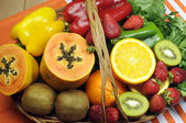 Healthy diet - sources of Vitamin C - oranges, strawberry, bell pepper capsicum, kiwi fruit, paw paw, spinack dark leafy greens and parsley. — Stock Photo