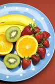 Bandeja de frutas - banana, laranja, fruta kiwi e morangos - bandeja azul polka dot para dieta saudável e fitness. vertical. — Fotografia Stock