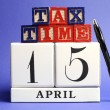 Save the Date, April 15, USA Tax Day with white calendar and red, white ad blue building block letters on blue background. — Stock Photo #21776435