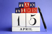 Save the Date, April 15, USA Tax Day with white calendar and red, white ad blue building block letters on blue background. — Foto Stock