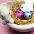 Pink and blue Easter eggs in white bunny bowl with heart gift tag on pink background. Vertical. — Stock Photo