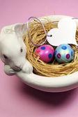 Rosa und blaue ostereier in weißen bunny-schüssel mit herz geschenk kennzeichnen auf rosa hintergrund. vertikale. — Stockfoto