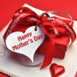 Red present gift with white heart shaped gift tag and ribbons and bow on a red background, with Happy Mothers Day tag. — Stock Photo
