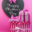 Stack of beautiful pink stripe and polka dot present gifts with heart shape blackboard with Happy Mothers Day message. - Foto de Stock