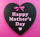Tablica kształt serca z różową wstążką na różowym tle z matek szczęśliwy dzień wiadomości. — Zdjęcie stockowe