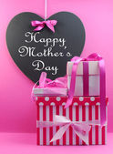 Stack of beautiful pink stripe and polka dot present gifts with heart shape blackboard with Happy Mothers Day message. — Stock Photo