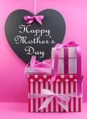 Stapel van mooie roze stripe en bolletjestrui aanwezig geschenken met hart vorm schoolbord met gelukkig moeders dag bericht. — Stockfoto