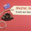Australian ANZAC Day, April 25, save the date with WW1 Rising Sun Hat Badge on red, white and blue background with Australian flag and Lest We Forget message tag. - Stock Photo
