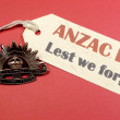 Australian ANZAC Day, April 25, save the date with WW1 Rising Sun Hat Badge on red, white and blue background with Lest We Forget message tag sign. - Stock Photo