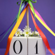 May Day, May 1, white block calendar with maypole and rainbow color ribbons and flowers against a purple background. — Stock Photo #22594021