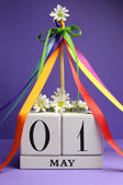 May Day, May 1, white block calendar with maypole and rainbow color ribbons and flowers against a purple background. — Stock Photo