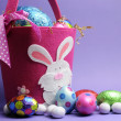 Royalty-Free Stock Photo: Pink and purple Easter egg hunt with bunny basket carry bag & eggs.