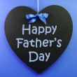Happy Fathers Day message written on a black blackboard with blue ribbon against a blue background. — Stock Photo #22993600