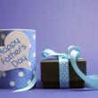 Happy Father's Day blue polka dot coffee mug for breakfast with black box present gift with polka dot ribbon and white heart shape tag with Happy Fathers Day message — Stock Photo