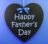 Happy Fathers Day message written on a black blackboard with blue ribbon against a blue background. — Stock Photo