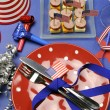 USA Happy Fourth 4th of July party table setting with flags, ribbons, polka dots, and stars and stripes decorations. — Stock Photo #23418920