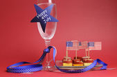 USA Happy Fourth 4th of July party table setting with flags, ribbons, polka dots, and stars and stripes champagne glass and cocktail food. — Stock Photo