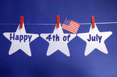 Happy Fourth 4th of July message written across three 3 white stars with USA American flag hanging on red pegs on a line — Stock Photo