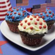 Fourth 4th of July party celebration with red, white and blue chocolate cupcakes on white heart plate and USA American flags - closeup. — Zdjęcie stockowe