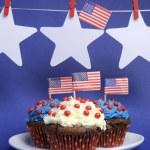 vierde 4 juli partij feest met blauwe, rode en witte chocolade cupcakes op witte breuk plaat en VS Amerikaanse vlaggen met sterren opknoping van pinnen op een regel met kopie ruimte. verticale — Stockfoto