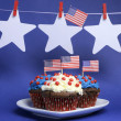 Fourth 4th of July party celebration with red, white and blue chocolate cupcakes on white heart plate — Stock Photo #23593627