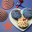 Fourth 4th of July party celebration with red, white and blue chocolate cupcakes on white heart plate  — Photo