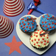 Fourth 4th of July party celebration with red, white and blue chocolate cupcakes on white heart plate  — Stok fotoğraf