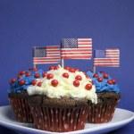 quatrième 4 juillet Fête de célébration avec des petits gâteaux au chocolat, rouge, blanc et bleu sur coeur blanc plaque et usa drapeaux américains — Photo