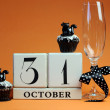 Happy Halloween save the date white block calendar with champagne glass and chocolate muffins with black cat decorations — Stock Photo