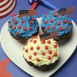 Fourth 4th of July party celebration with red, white and blue chocolate cupcakes on white heart plate — Stock Photo #23593711