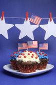 Fourth 4th of July party celebration with red, white and blue chocolate cupcakes on white heart plate and USA American flags with stars hanging from pegs on a line with copy space. Vertical. — Stock Photo