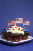 Fourth 4th of July party celebration with red, white and blue chocolate cupcakes on white heart plate and USA American flags — Stock Photo