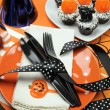 Happy Halloween party table with orange polka dot plates and chocolate cupcakes - Stock Photo