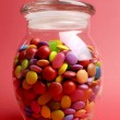 Glass Jar full of bright colorful lollies and candy with closed lid for Christmas or Halloween treats. - Stock Photo