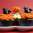 Happy Halloween orange and black decorated cupcakes with black cats and pumpkin jack-o-lanterns — Foto Stock