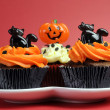 Happy Halloween orange and black decorated cupcakes with black cats and pumpkin jack-o-lanterns — Stock Photo