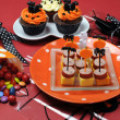 Happy Halloween party table with skeleton glass, cupcakes, candy lollies and party food with orange and black pumpkin, cat, bat and ghost decorations. — Stock Photo