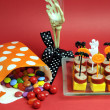 Stock Photo: Happy Halloween party food with skeleton hand glass on red background.