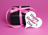 Special small black box present gift with pink polka dot ribbon and white heart shape gift tag with for Mothers Day, with message. — Stock Photo
